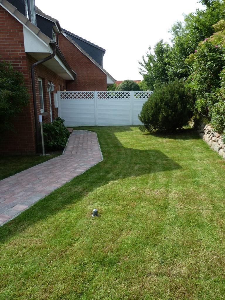 Grundstück nach Kundenwunsch mit Betonplatten Kunststoffzäunen und Rollrasen